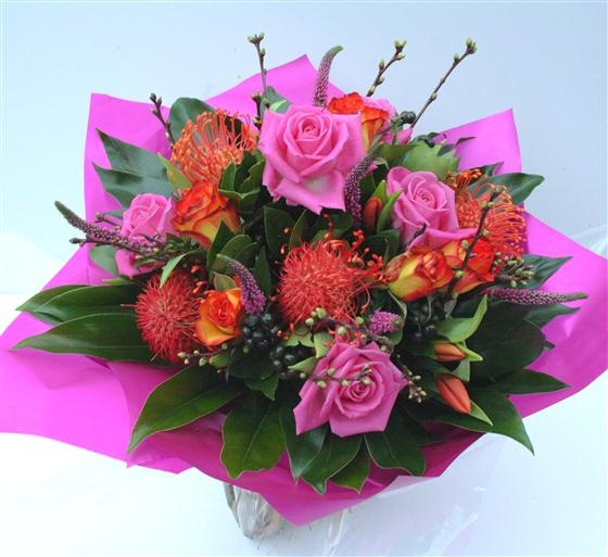 This bouquet is named Joyful! A mixture of pink roses, burnt orange roses, leucospernum, orange tulips, pink veronica and blossom. #Joyful #Flowers