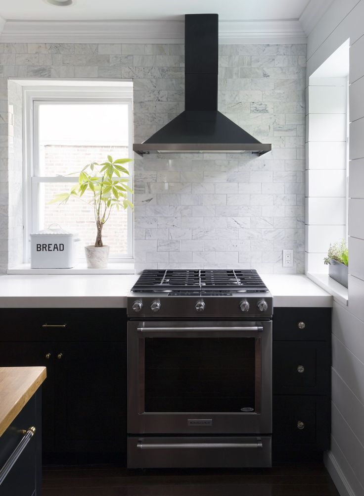 Black Kitchen With Full Wall Of White Marble Tile Black Range Hood With  Stainless Stove