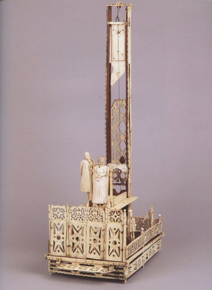 """""""An Unusually Large Napoleonic Prisoner of War Carved Bone Working Model of the French Revolutionary Guillotine: The recubent figure of the Queen, Marie Antoinette, lying on a podium below the table her decapitated head rolling into a waiting basket. A priest by her side providing the last rites, waiting guards below with moveable arms, late 18th Century. """"  Image from """"Camera Secreta: Auction catalogue from Finch & Co, 2014"""".  This book is part of the Morbid Anatomy Library Collection."""