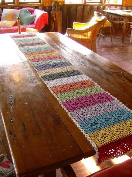 caminho de mesa de crochê. Feito de barbante tingido com cores alegres e variadas. O preço de UM METRO é de 60 reais. Foto ilustrativa com dois metros. R$ 60,00