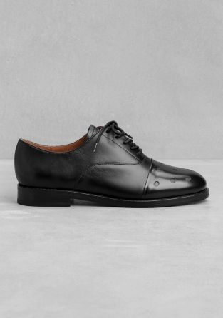 Chunky leather flats featuring a perforated front, a lace-up style, and an overall masculine feel.