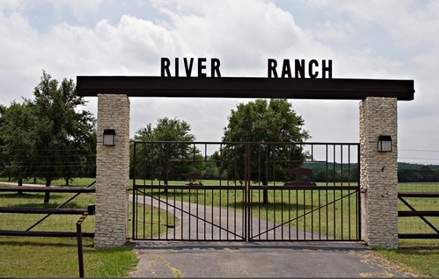 high stone columns with bold header bar with or without name above. Tall iron gate and Steel pipe fencing and hog wire.