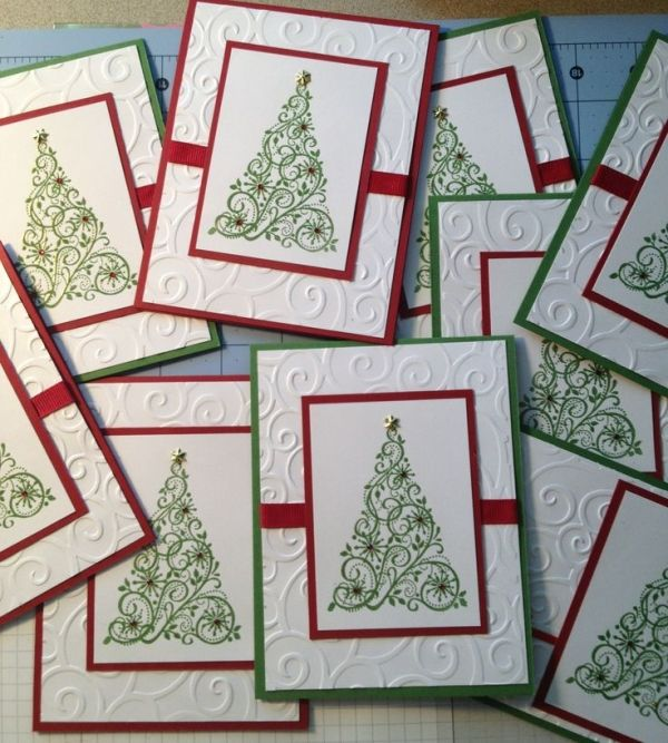 By Natalie Badolato. Christmas card. White dry embossed panel with horizontal ribbon attached was adhered to red or green card base. Tree stamped in green on smaller white panel & attached to red panel to frame it. This piece then attached to rest of card. Gems added to tree. Card easily mass produced. by artwear