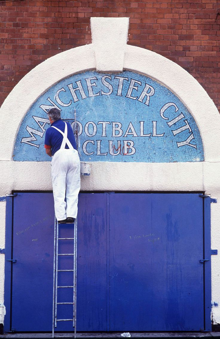 A Man City sign gets a fresh coat of paint at Maine Road, Manchester, England, United Kingdom, 1991, photograph by Colorsport (photographer unattributed).