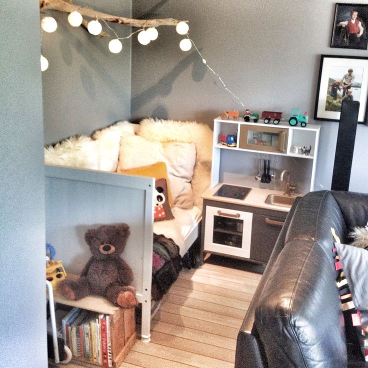 Kids corner in our living room. IKEA duktig kitchen and bed. Crates as storage and bookshelves. A piece of wood to hang the lights.