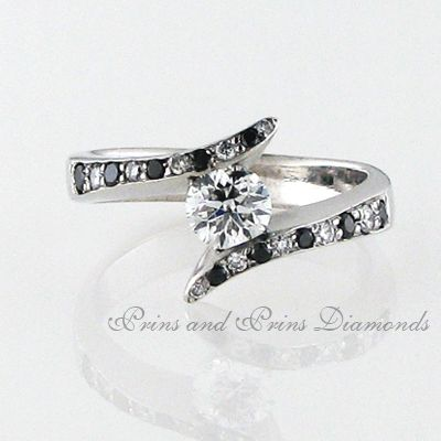 The centre stone is 0.554 F/SI2 round brilliant cut diamond tension set in a 18k white gold with 0.18ct alternating black and white round cut diamonds on the shank