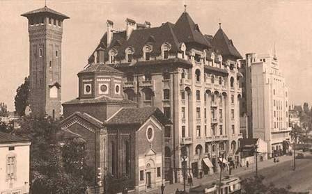 Fotografie de pe bulevardul Bratianu (actualul Balcescu). In imagine putem vedea Biserica Italiana, Palatul Societatii Actiunea Economica (cu turnurile de dinaintea cutremurului din '77; cladirea a fost proiectata de Leon Silion si finalizata in 1925) si o parte din blocul modernist Sun-London (in partea dreapta). Ne aflam asadar candva in anii '30.