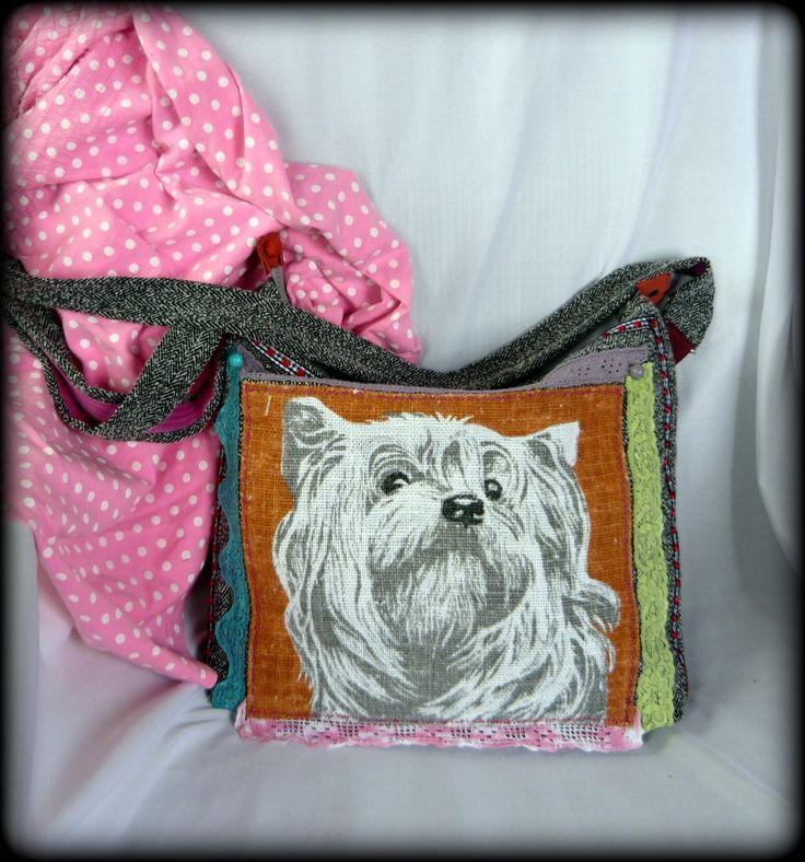 Handmade by Judy Majoros:Tarisznya formát kapott, ez a kutyusos táska. Egy halszálka mintás pamutvászon nadrágból készült ez a táska, melyre egy kutyafejet mintázó, vászon anyag került. Színes csipkékkel díszítettem, valamint gyöngyökkel. A táska cipzárral záródik. A hátulján egy bevarrt zseb található. Belseje viszkózzal bélelt, és két zseb került bele.A pántja a táska anyagából készült, pink szalaggal díszítve, valamint állítható, így vállon vagy keresztben is hordható.