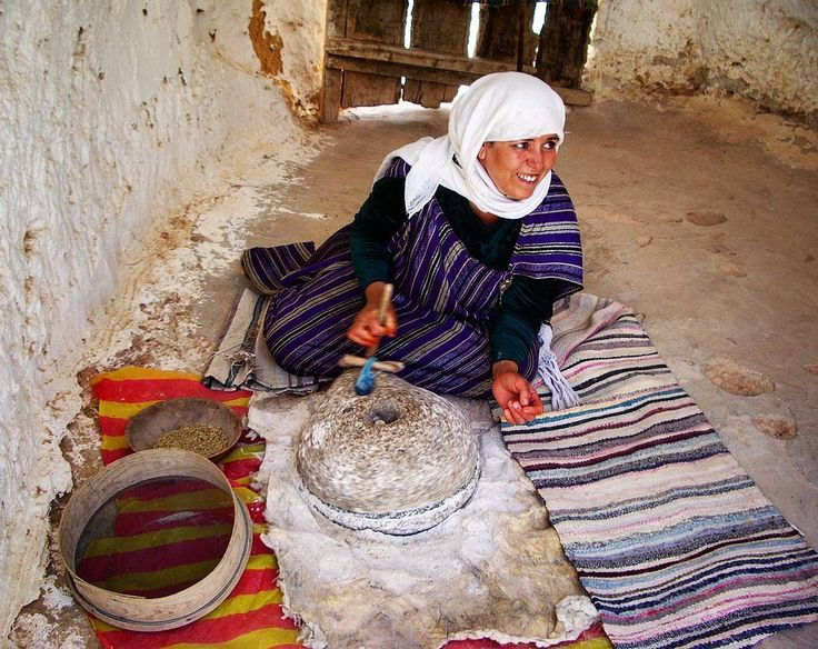 A woman is grinding grains  into flour in a berber house in Matmata Tunisia.