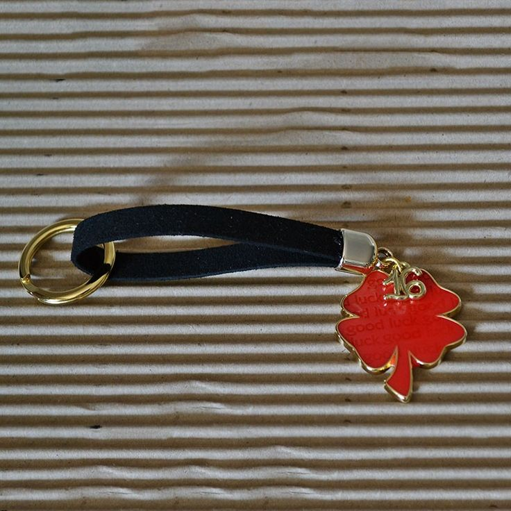 Γούρι μπρελόκ κόκκινο μπρούτζινο, τετράφυλλο τριφύλλι, που γράφει πάνω good luck, σε μαύρο λουράκι και μπρούτζινο κρίκο.