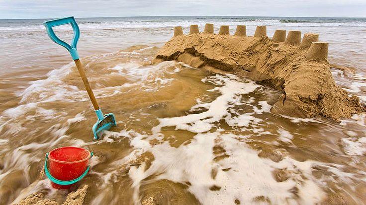 Sandburg überflutet-Was passiert bei Ebbe und Flut?  Dass der Mond für Ebbe und Flut verantwortlich ist, wissen viele. Doch wie genau macht er das? Und warum zieht sich das Meer an der Nordsee viel weiter zurück als am Mittelmeer?