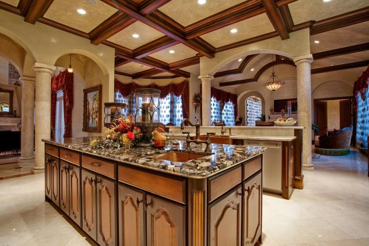 The luxurious kitchen features a spacious wood island with a sink, ensuring the chef has plenty of prep space. A gorgeous coffered ceiling extends beyond the kitchen, connecting the space to the adjoining dining and living areas.