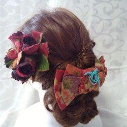 着物帯の変わり結び;立て矢結び花びら添えを型どったヘアアクセサリーと真紅の薔薇の花をセットにしたヘッドドレスです。着物帯結びを型どったアクセサリーは珍しく、和装の時には実際の帯結びと合わせてもお洒落感が増すのではないかと思います。大柄の牡丹で華やかな印象の柄になっています。大きめのヘッドドレスに仕上げており、存在感があります。クリップを使用することで、ショートヘアにも飾って頂けると思います。共布でダリアのアーティフィシャルフラワーの髪飾りをセットにしています。ミニクリップが付いておりますので、ブローチ・コサージュとしてもご使用頂けます。バッグにチャームとして飾ってもインパクトがあります。成人式や卒業式、和装婚、パーティーなどを華やかで存在感があり、かつ上品に彩ってくれると思います。クリップ;13,5cm×8,5cmアーティフィシャルフラワー;11cm×11cm…