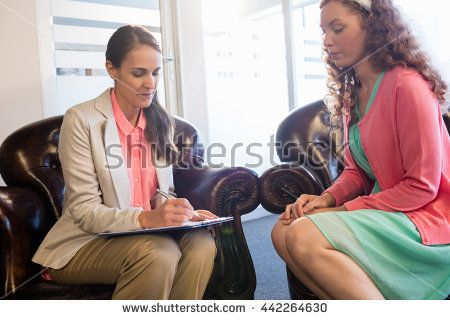 Beautiful young woman discussing with psychologist in office