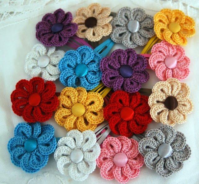 crochet flower pattern--shown here attached to hair clips but lots of decorative uses---crochet a long chain stitch tail for a bookmark; attache a safety pin on back for a brooch or bag pin, etc.