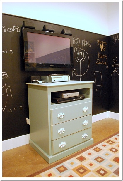Dresser / Chester Drawers made for TV and area for receiver/DVD.  I would put hinges on the drawer front  that would open flat when watching TV.