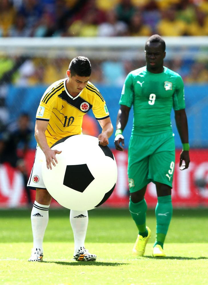 Colombia Holds Off Ivory Coast 2-1 In Furious Finish At World Cup - BRASILIA, BRAZIL - JUNE 19: James Rodriguez of Colombia deflates a large inflatable football during the 2014 FIFA World Cup Brazil Group C match between Colombia and Cote D'Ivoire at Estadio Nacional on June 19, 2014 in Brasilia, Brazil. (Photo by Warren Little/Getty Images)