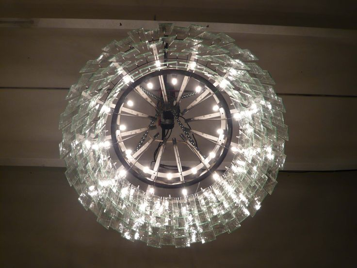 LAMPADARIO DONUTS / DONUTS CHANDELIER sizes 97 X 97 X 50 Donuts Chandelier made with steel structure and glass plates. Equipped with black iron ceiling rose. Orvett Design