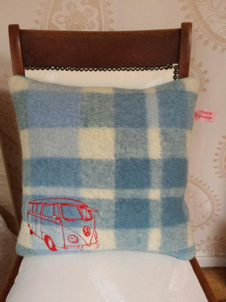 Dit kussen is in opdracht gemaakt voor een heel bijzonder persoon. De voorzijde is vintage deken en de achterzijde een bijpassende blauwe stof. Afgewerkt met een zelfde blauwe paspelrand. Door de ondergrond rustig van kleur te houden, springt het rode busje er goed uit.
