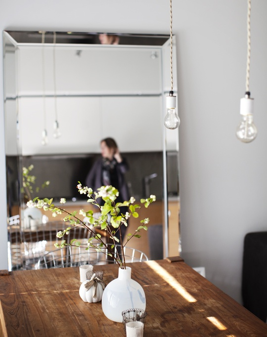 timber table + bare bulb pendants + large leaning mirror in dining space by the cross design