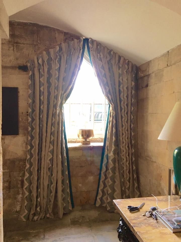Curtains for a shaped window by Fiona Tait Interiors.