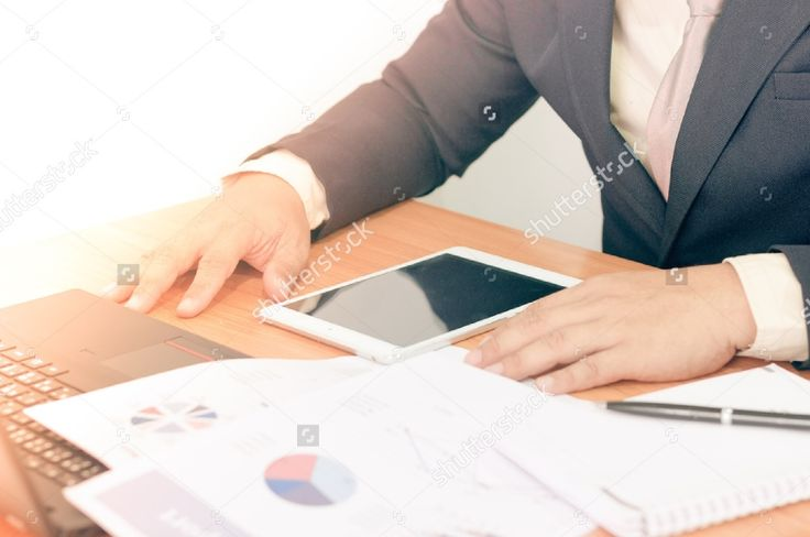Businessman working on office desk. Writing something on notebook.Watching something on tablet. Blurred background, Vintage concept. #business #businessman #man #professional #office #background #notebook #tablet