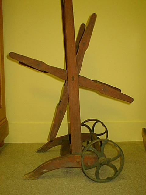 This is a very rare find--a late Victorian water hose reel. It is made of hardwood. The grain appears to be hickory, but the old red paint maks it difficult to tell. The wheels are cast iron and have a beautiful design for such a functional piece. The reels turn and the cross boards are doweled into the arms. This reel was used either for a garden hose or a water hose used by a rural fire station. Great piece of Americana.