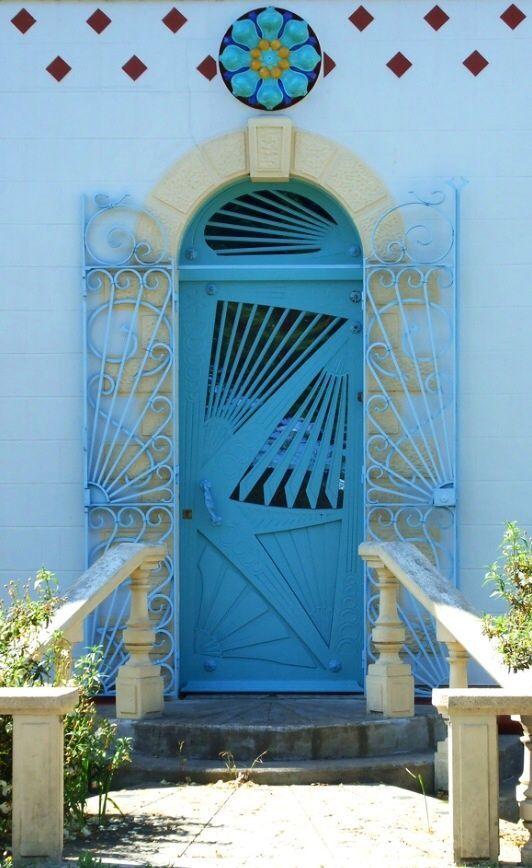 Голубые двери с геометрическими узорами и кованными ставнями