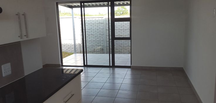 Inside view of the kitchen/living room, with sliding door leading on to undercover patio.