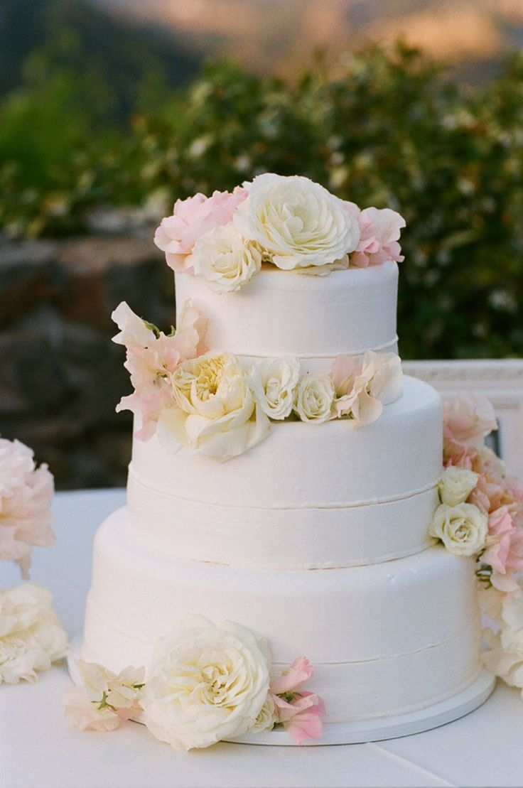 Simple #wedding #cake. Plan white with accent provided by flowers matching the bride's bouquet. Plan your wedding for free online at www.Jellifi.com