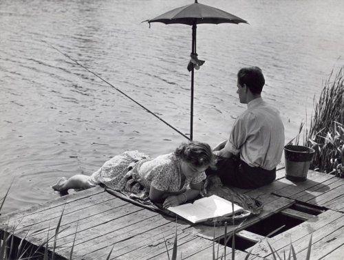 Man zit te vissen (hengelen) en vrouw ligt te lezen, samen op een steiger onder een paraplu, Nederland, 28 mei 1954.
