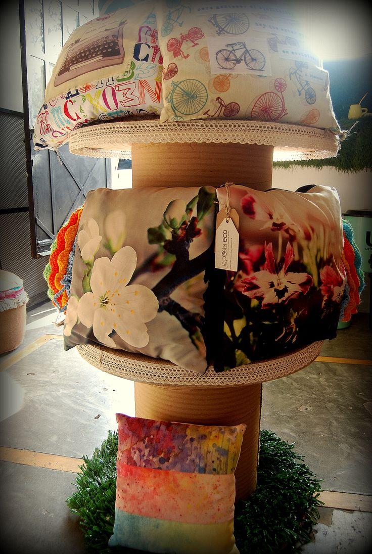Exposición de almohadones en vidriera central de la eco-tienda