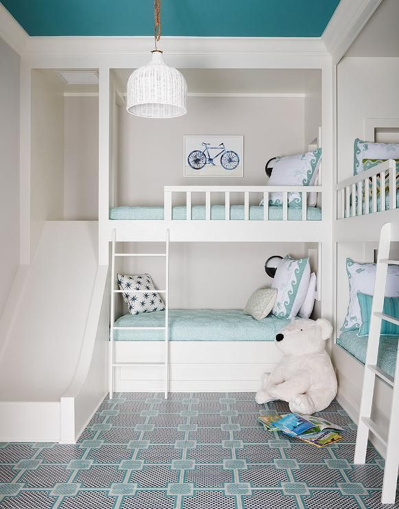 Aqua blue shared girl and boy's bedroom features two sets of built-in bunk beds dressed in aqua bedding and pillows illuminated by black and white wall sconces.