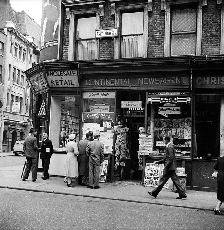 12 June 1956: People look at notices outside a newsagent's shop on Frith Street, where a newspaper board reads: 'They saved London'