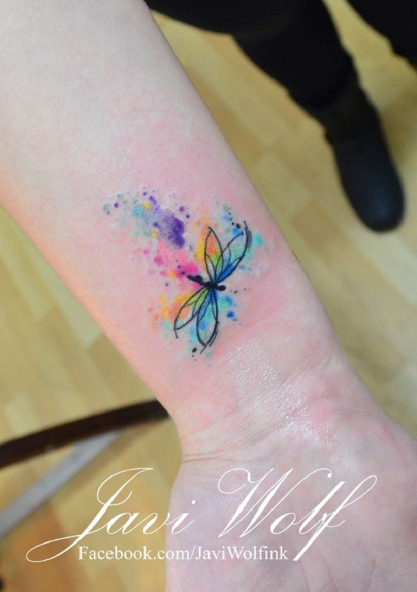 A very cute and minimalist dragonfly tattoo on the arm. The dragonfly is simply drawn in circles and lines and it leaves a blast of multi colors as it glides through the air flying.