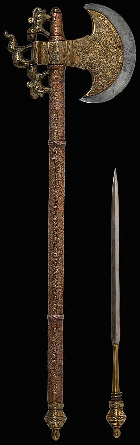 Indian tabar (axe), 19thc, crescent shaped steel blade covered in brass and decorated with engraved arabesque motifs. In the counter blade it has an elephant surrounded by two tigers, in a perfect silhouette, made of forged brass. The tubular handle is completely covered in brass, ornamented with a vegetal themed chisel work. It is finished by a lotus button which serves as a handle for a small dagger hidden inside it. Full Length: 56 cm; Axe's Blade Length: 13 cm; Dagger's Blade Length: 26…