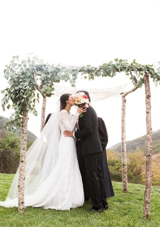 wooden chuppah accentuated with asymmetrically placed foliage