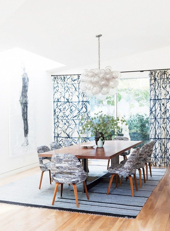 Gray tone modern dining area with glass bulb chandelier, upholstered midcentury dining chairs, and wooden table.
