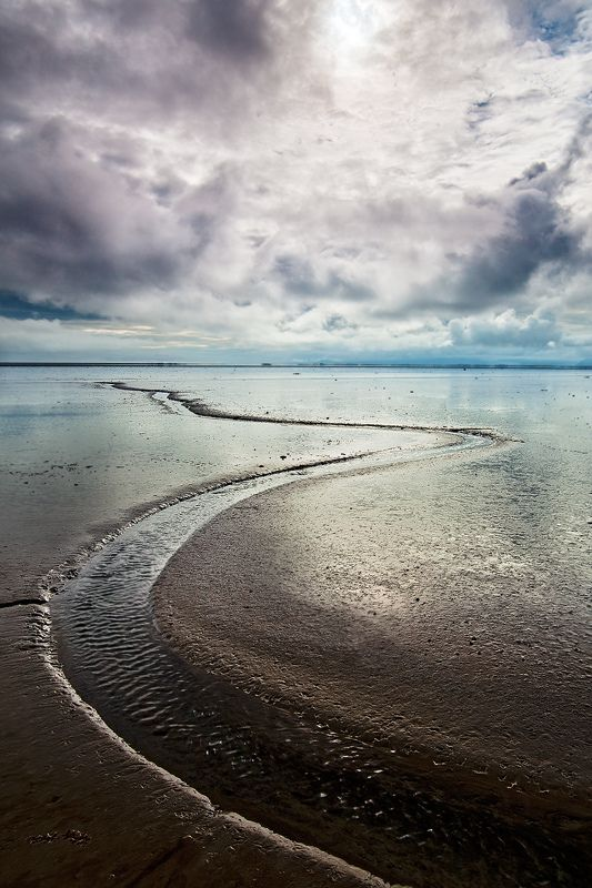 Iceland - Eastfjords: 12 Hour River  A river winds itself through a mud field at low tide. The river disappears at high tide, only to be revealed in a new form at low tide.