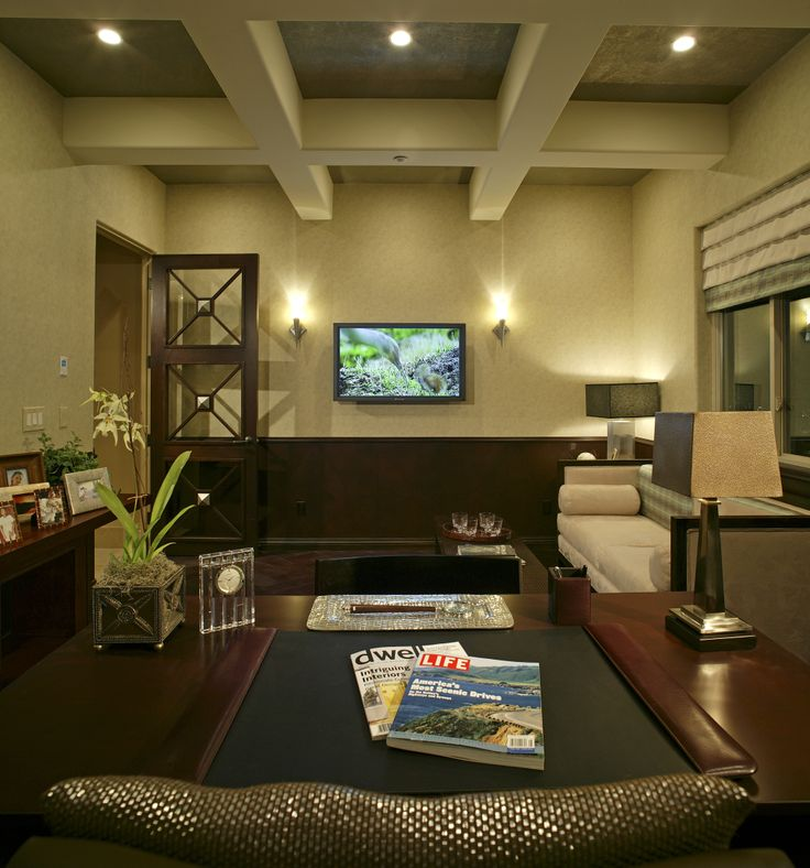 The perfect home office with dark wood paneling, mounted TV, neutral walls and of course, and a large office desk.