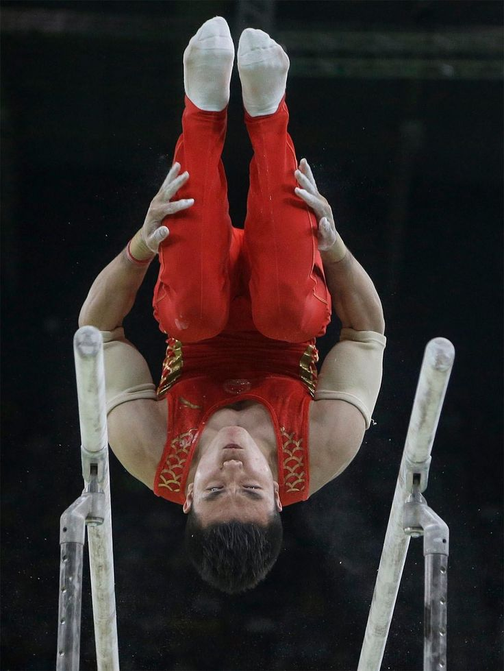 China's Lin Chaopan performs on the parallel bars during the artistic gymnastics…