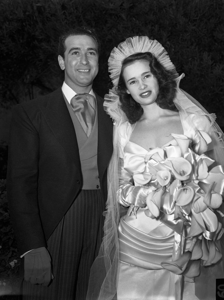 """The couple: Gloria Vanderbilt and Pasquale DiCicco When: December 25, 1941 Where: Ceremony at the Santa Barbara Mission, reception at the home of Thelma Furness in Beverly Hills Her dress: Draped and décolleté satin of white slipper satin """"in the style of 1890"""" by Howard Greer; a 24-foot veil-train Her flowers: Calla lilies The headlines: """"Wedding of Young Heiress Takes Place Amid Typical Movieland Setting"""""""