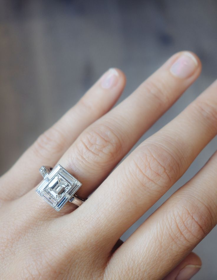 Antique Art Deco engagement ring made in platinum and centered with an EGL certified approximately 1.40 carat emerald cut diamond with F-G color and VS2 clarity. Accented with eight baguette cut diamo