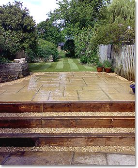 'Wide Steps These steps were created using new landscaping sleepers. The gravel strip at the base of the first step acts as a drainage channel for rain water from the existing patio, which slopes towards the steps. Gravel was also used behind the sleepers to create a wider tread, and a new patio and lawn were laid beyond the steps.'