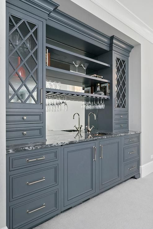 Gray wet bar cabinets painted in Benjamin Moore Ashland Slate are fitted with nickel pulls and a gray quartzite countertop holding a small square sink with a polished nickel gooseneck faucet in front of a mirrored backsplash finished with built in shelves flanked by gray lattice glass front cabinets.