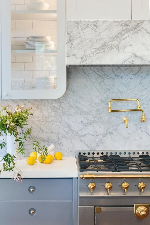 Gray kitchen features light gray upper cabinets, with backs of cabinets lined with white subway tiles, and dark gray lower cabinets paired with marble countertops and backsplash.