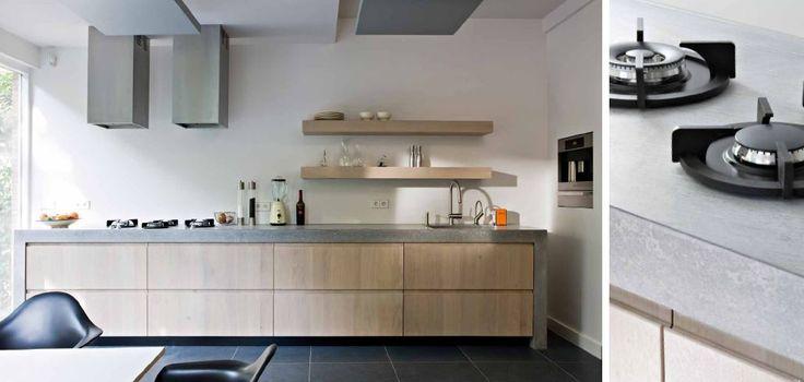 Maatwerk landelijk modern massief 3-laags eiken houten keuken met ter plaatse gegoten betonnen aanrechtblad doorlopend in zijwanden. Pitt Cooking kookplaat oven vaatwasser en koelkast verwerkt in de muur. Afzuigkappen op maat gemaakt - The Living Kitchen by Paul van de Kooi
