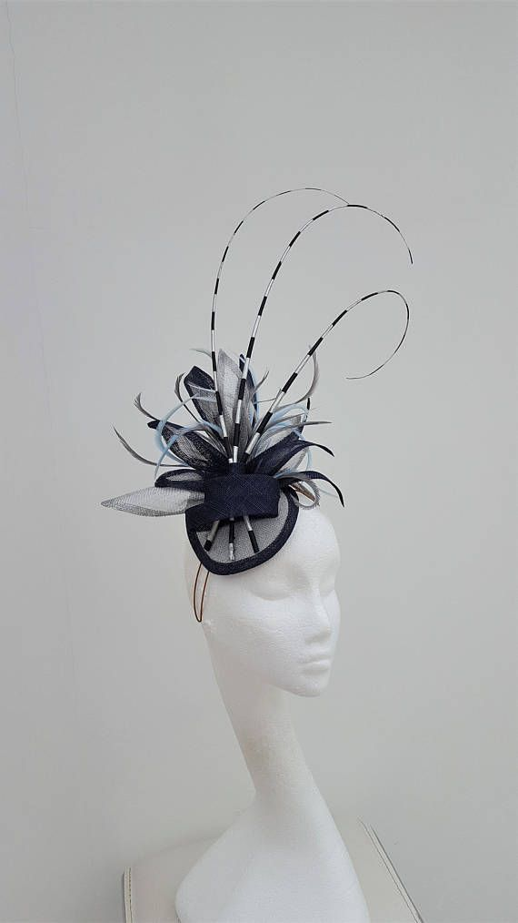 Striking fascinator in navy and silver sinamay. A trio of hand painted  silver and navy curled ostrich quills burst from a cluster of s… edf3403d037