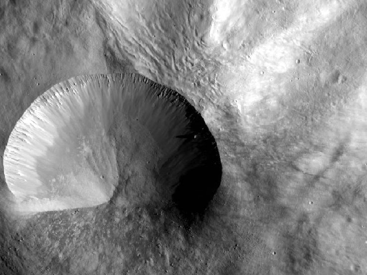 This image from NASA's Dawn spacecraft shows a young crater on Vesta that is 9 miles (15 kilometers) in diameter. Layering is visible in the crater walls, as are large boulders that were thrown out in the material ejected from the impact. This image was obtained by Dawn's framing camera image was acquired on Dec. 21, 2011.