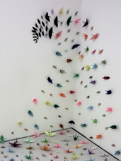 Colorful origami birds attached to a wall all follow a pattern that looks surreal and looks as if their ready for take off!